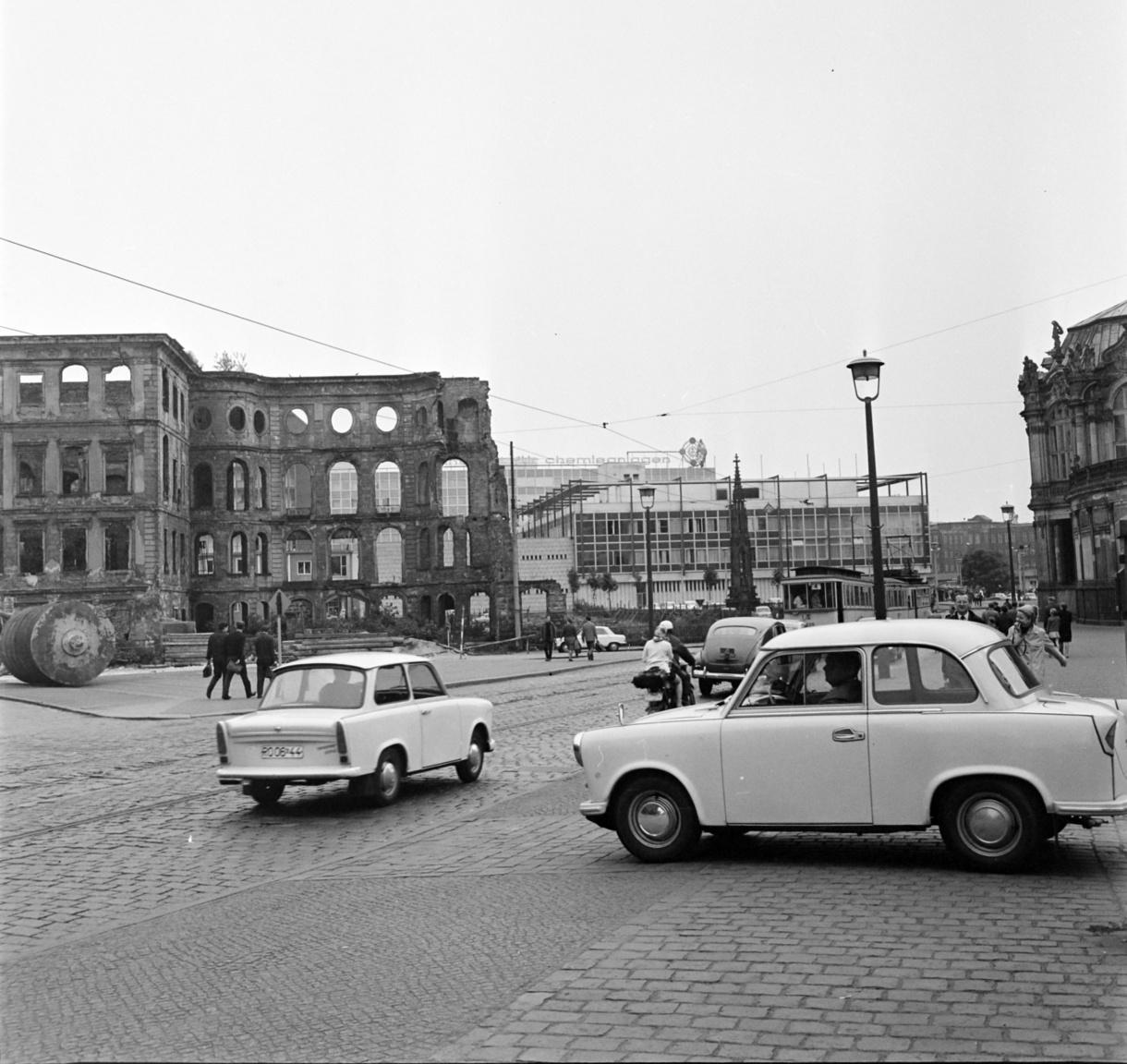 Talán nem is lehetne jobban kifejezni egy képben a hatvanas évekbeli NDK helyzetét: a háttérben még mindig háborús romok, az utcán viszont már ott pöfög a Trabant két generációja: balra a legendássá vált autó egyik hatvanas évek eleji szériája (talán egy Trabant 500-as) jobbra pedig ott hasít a Magyarországon is tömegesen elterjedté vált 601-es. Az anyaghiánnyal küzdő ország által gyártott autó már a tervezésekor is elavultnak számított, mégis sokan szerették, mert olcsó és könnyen javítható volt.