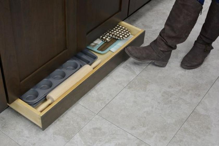 Ötletes rejtett tárolót lehet kialakítani a konyhapultok alá is. Kinek jutna eszébe egy fiókot keresni még a lábazatnál? Ugyanakkor méretétől függően akár konyhai eszközöket is lehet benne tartani.