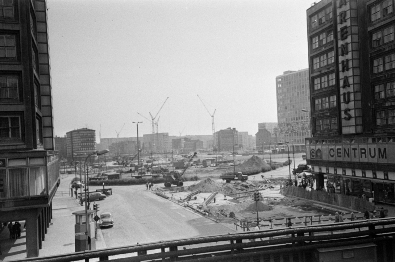 As construction of Berlin's TV tower began, the centre of East-Berlin was completely transformed: the historic buildings of Alexanderplatz were all demolished except for the Marienkirche and the Rotes Rathaus. The grey, cubical houses erected in their stead turned the area into a real phalanstery, although the cubical building seen in the front of the picture above still stands out despite its angular shape: it is Berolinahaus, a classic product of 1930s modernism.