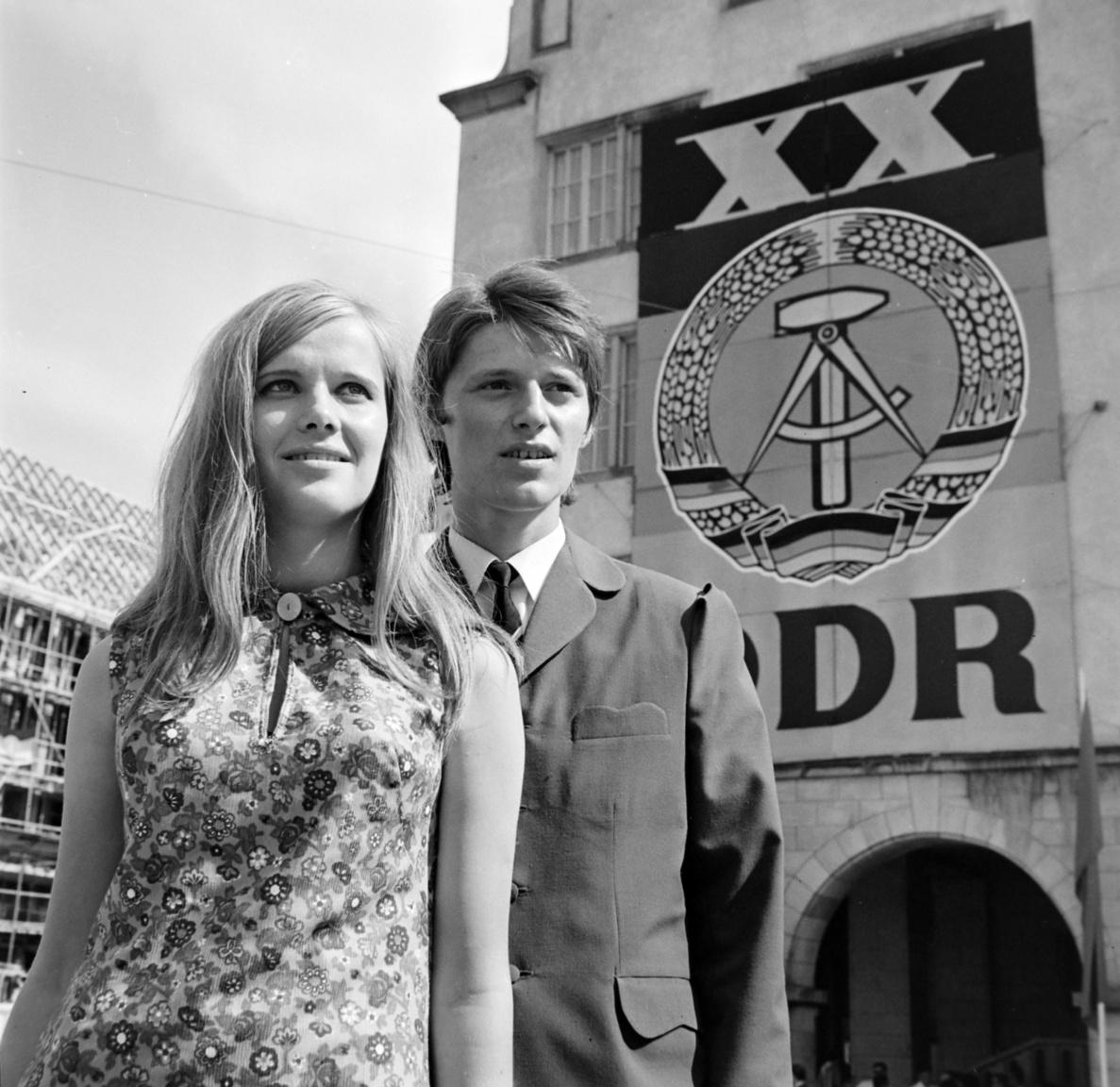 1969 - az NDK 20 éves évfordulója optimista arcú fiatalokkal. A fiatal nőn a fejlett német műanyagipar jellegzetes terméke, a műszálas ruha, ami dörzsölés hatására szikrákat hányt a sötétben.