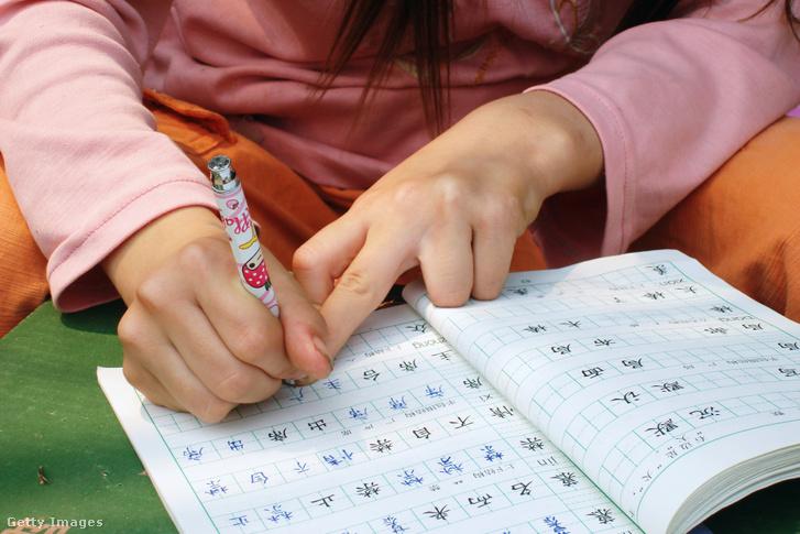 Házifeladatot ír egy kínai iskolás gyerek.