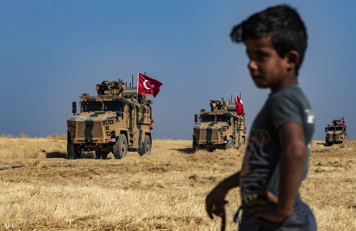 Szíriai fiú figyeli a török katonai járműveket az al-Hashisha falunál, közel a török határhoz 2019. október 4-én