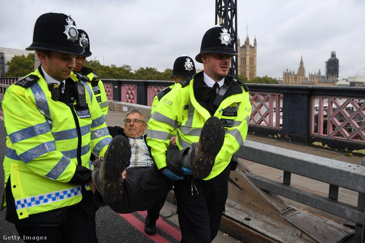 A rendõrség eltávolít egy tüntetõt a Lambeth Bridge-bõl 2019. október 7-én, Londonban