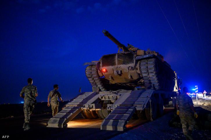 A török hadsereg tankja lehajt egy teherautóról, amikor a török fegyveres erők Szíria határa felé haladnak a Sanliurfa tartomány Akcakale közelében, 2019. október 8-án.