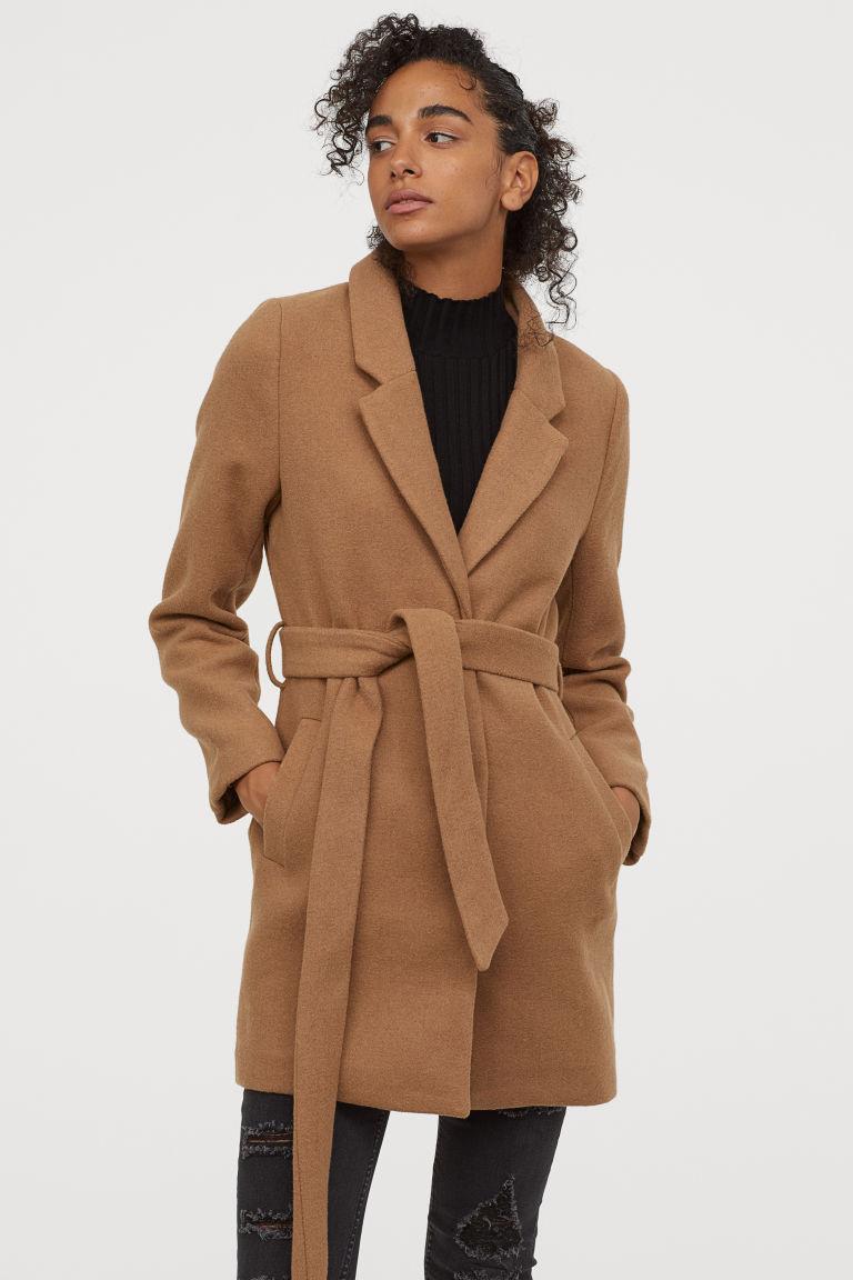 A H&M kötős, teveszínű szövetkabátja elegáns, nőies, és karcsúsítja, nyújtja az alakot. 14 995 forintért lehet a tiéd.