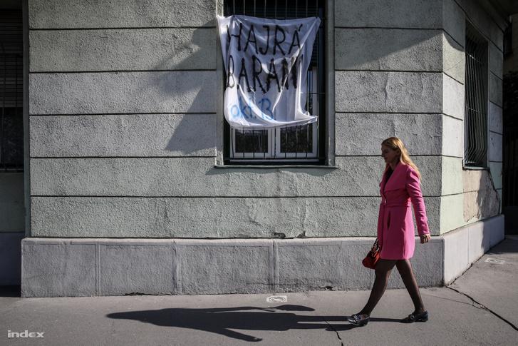 Baranyi Kriszta sétál el egy őt támogató ablakra kifüggesztett felirat mellett
