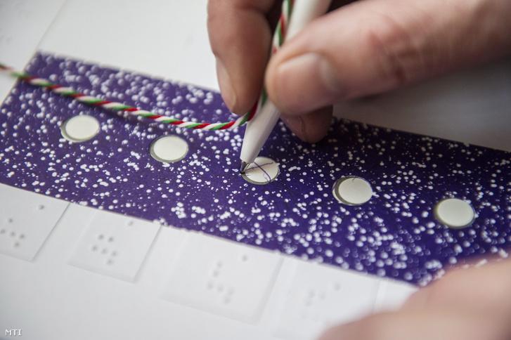 Egy látássérült Braille-írással ellátott szavazósablont használ szavazata leadásához az országgyűlési képviselő-választáson 2014. április 6-án