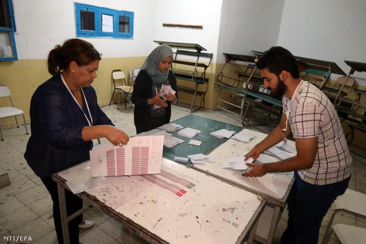 A szavazatszámláló bizottság tagjai számolják a szavazólapokat az elnökválasztás második fordulója után egy tuniszi szavazóhelyiségben 2019. október 13-án.