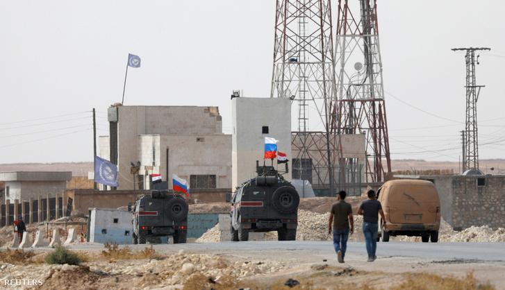 Orosz és szír zászlókkal vonuló katonai járművek Manbídzsnél kedden