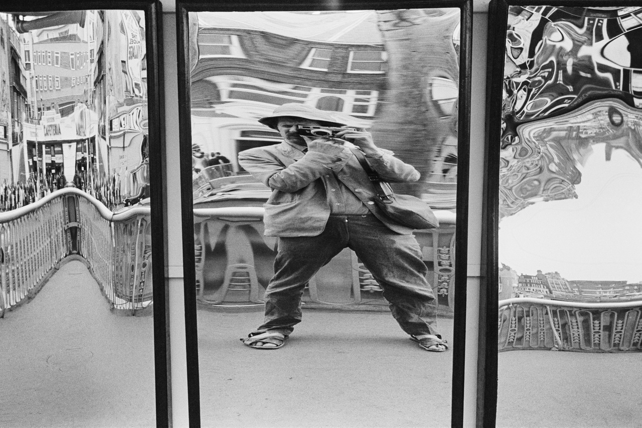 """Jonesnak nagy gyűjteménye volt századfordulós képeslapokból, amik a nagyobb strandokat ábrázolták.                          Feljegyezte a legfontosabb alapvetéseket, miszerint egy jó fotós türelmes, beszélget az emberekkel, változtatja a szögeket és a beállításokat, közel megy, nem lő túl sok képet, és ami a legfontosabb, hogy nem csinál unalmas képeket.                          Tony Ray-Jones 1972-ben halt meg, ez a  """"tükrös szelfi"""" az 1960-as évek végén készült róla."""
