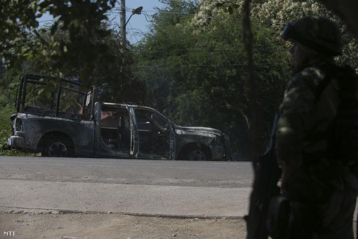 Felgyújtott rendőrségi jármű útszéli roncsánál áll egy katona a nyugat-mexikói Michoacán állambeli El Aquaje városban 2019. október 14-én