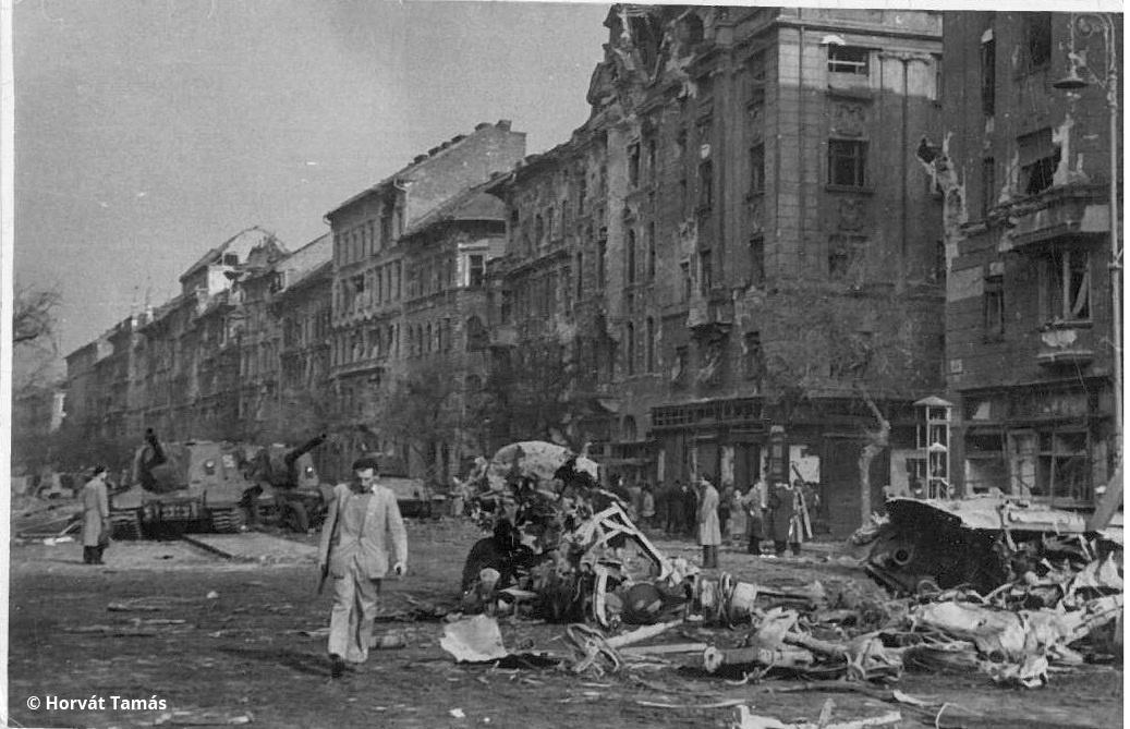 A legsúlyosabb harcok az Üllői út - Ferenc körút kereszteződése környékén, a Kilián laktanyánál és a Corvin közben voltak. A képen kezében fegyverrel közeledő férfi jó eséllyel szintén a Corvin köziek közé tartozott. A háttérben kiégett tankok és Joszip Sztálin szovjet önjárók roncsai.