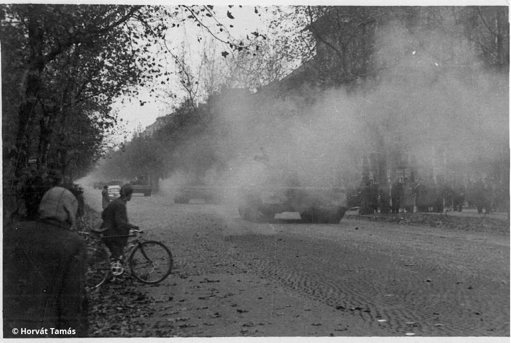 """Szovjet harckocsioszlop hagyja el Budapestet, talán a Népköztársaság útján (ma: Andrássy út). A legvalószínűbb időpont október 29. délután, ekkor kezdődött a szovjet """"kivonulás"""", amiről akkor úgy tűnt, a forradalom győzelmét jelenti. Másnap az oroszok úgy döntöttek, visszatérnek, ami november 4-én be is következett, a forradalom bukását hozva magával."""