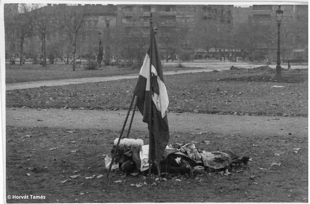 Szintén a Köztársaság tér: elesett felkelő letakart holtteste lukas zászlóval, halottak napi krizantémmal.