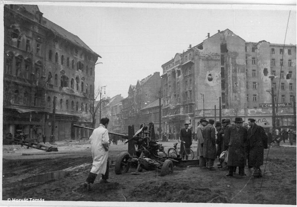 Ugyancsak a Baross tér, a lencse ezúttal a Rákóczi út felé néz. A felkelők november 3-án felállított ágyúját a Vörös Hadsereg hamar szétlőtte, a felkelők bázisa a Baross tér 19. számú háza még egy napig tartott ki.