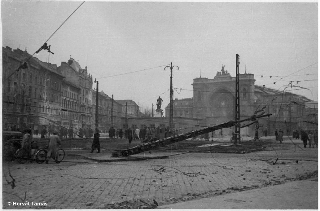 Az eddigi képek a forradalom napjait mutatják, az ismeretlen fotós azonban a szovjet bevonulás, a forradalom eltiprása után is folytatta a fényképezést. Sorozatunk utolsó három kockája valószínűleg november közepe után készülhetett, amikor a maradék ellenállást az oroszok nagyrészt már felszámolták, a harcok pusztítása azonban ott volt mindenhol. Itt: löveg és kidőlt villanyoszlop a Keletinél, a pályaudvar előtti földszintes építmény a félbemaradt metróépítés barakkja lehet.