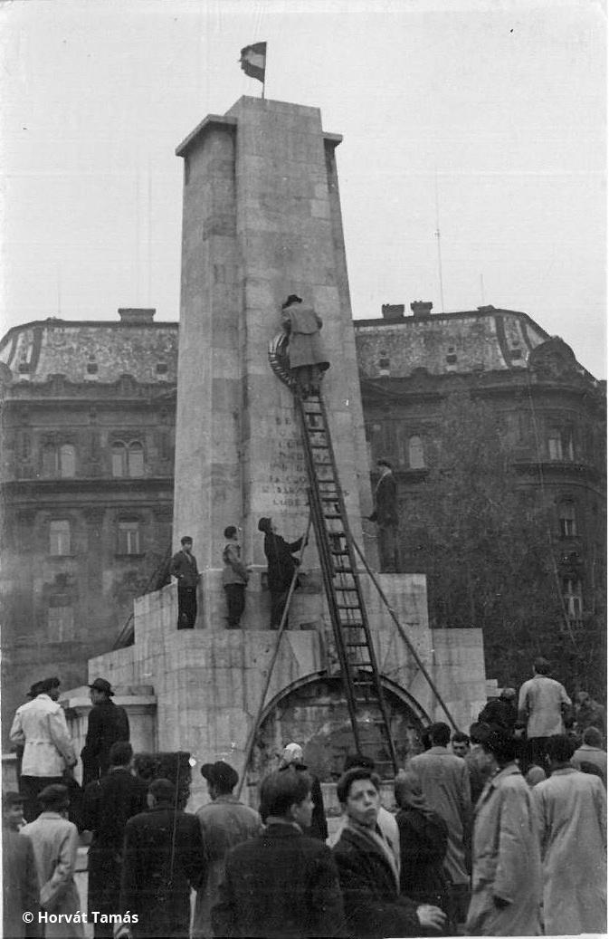 """A Szabadság téri szovjet emlékmű címertelenítése tűzoltólétráról, fent már magyar nemzeti a lobogó. Október 23. talán a Sztálin-szobor ledöntésével lett tüntetésből forradalom, és '56-nak nagyon sok településen is a jelképrombolás volt a kulcseseménye. A Szabadság téren a ma is látható szovjet emlékművön kívül állt egy szovjet szobor is, egy moszkvai másolata, amit még Sztálin """"adott ajándékba"""" a magyar dolgozóknak. Az allegorikus kommunista család emlékművét nem állították helyre a forradalom bukása után sem, szemben a ma is álló, körbekerített szovjet emlékművel."""