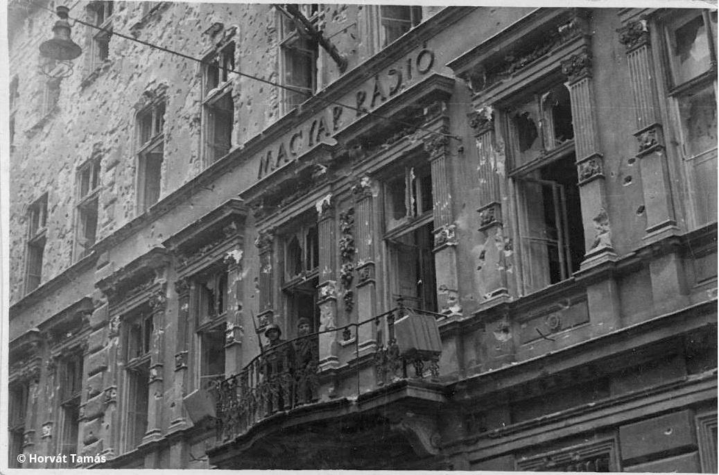 """A Magyar Rádió Bródy Sándor utcai székháza, az első, október 23-i fegyveres harcok helyszíne. A lukacsosra szaggatott épületet az oroszok 25-én foglalták vissza, majd a """"tűzszünetben"""", október 29-től a piliscsabai páncélosok vették birtokba Solymosi János parancsnoksága alatt - valószínűleg az ő katonáit látjuk az erkélyen. A homlokzatra hamarosan kiírták, hogy SZABAD Magyar Rádió, ezt itt még nem, de a hangszórókat láthatjuk. Az adást a forradalom napjaiban nem innen, hanem a parlamentből sugározták."""