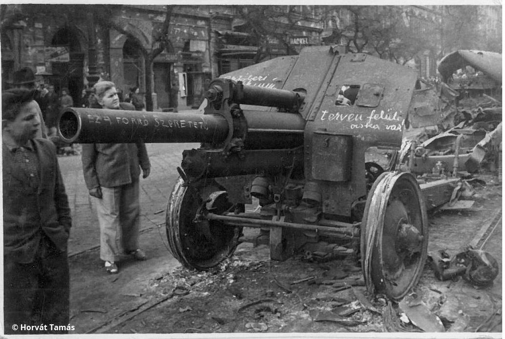 """""""Terven felüli ócska vas"""" """"ez a forró szeretet""""  - a forradalmi graffiti egy kilőtt szovjet lövegre firkálva hirdeti a szovjet-magyar barátság elképzelt jövőjét a következő ötéves tervre. A körúti villamossínen álló roncs körül bámészkodók, valószínűleg az átmeneti fegyvernyugvást és össznépi optimizmust hozó hozó október 29-31. közötti napok valamelyikén járunk."""