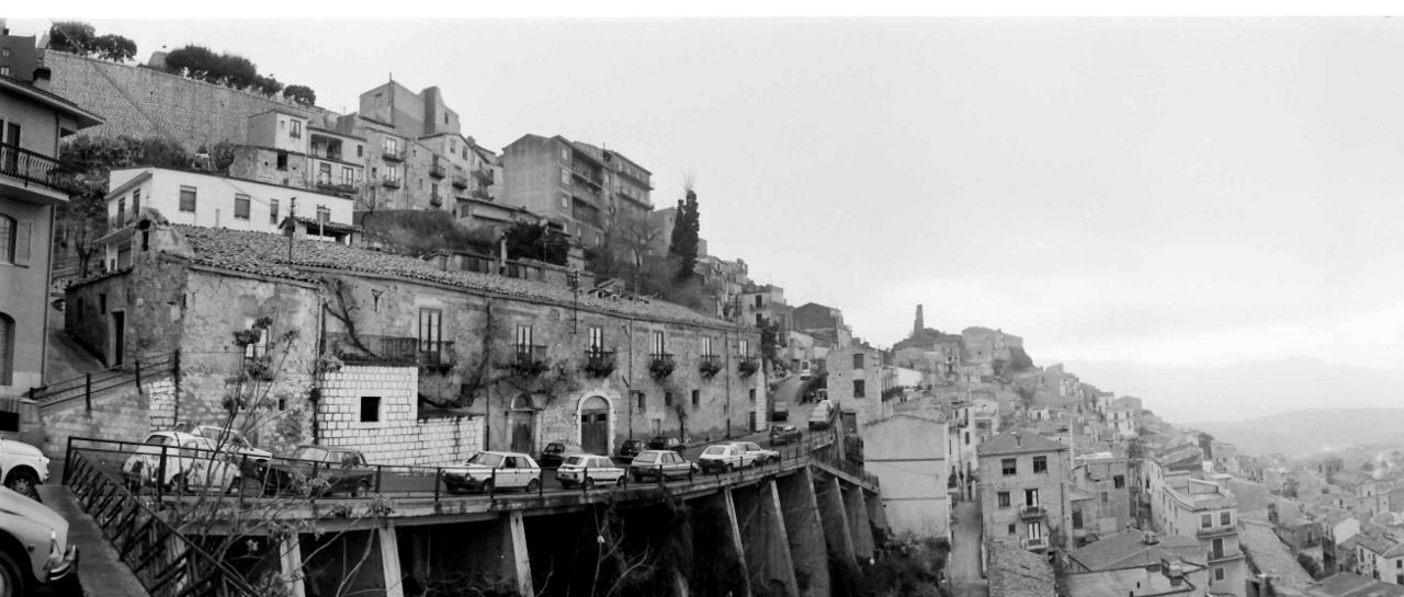 """A szicíliai Cammaratában. Az olasz-magyar koprodukcióban forgatott A menyasszony gyönyörű volt című filmhez készült helyszínfotó, 1987.Kendéék a maffiával is kapcsolatba kerültek a szicíliai forgatáson. Előbb megnehezítették a dolgukat, majd miután megkapta a szerepet a maffia pártfogoltja, kezdődött a dolce vita. """"Letettem a fényképezőgépem egy asztalra, négy nap múlva is ott volt; ha a forgatás során költözni kellett, rögtön ott volt a rendőri felvezetés""""– mesélte az Indexnek."""