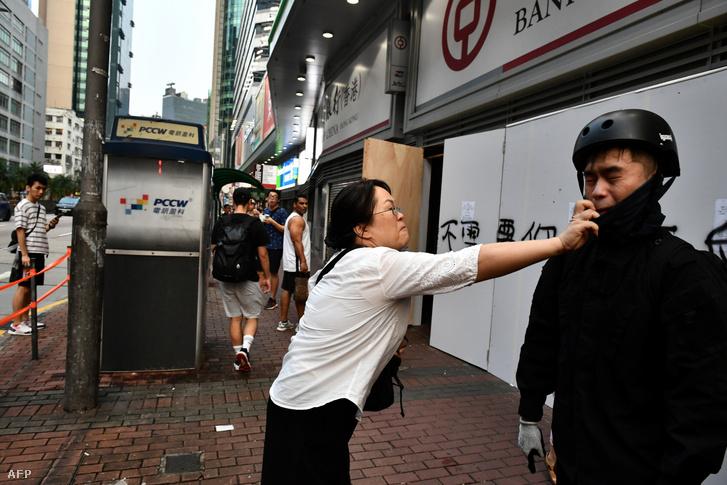 Egy nő próbálja meg letépni egy tüntető arcáról a maszkot Hong Kong Sham Shui Po kerületében 2019. október 12-én, miután a hong kongi kormányzó néhány nappal korábban bejelentette, hogy tilos az arcot eltakaró maszkot viselniük a demonstrálóknak