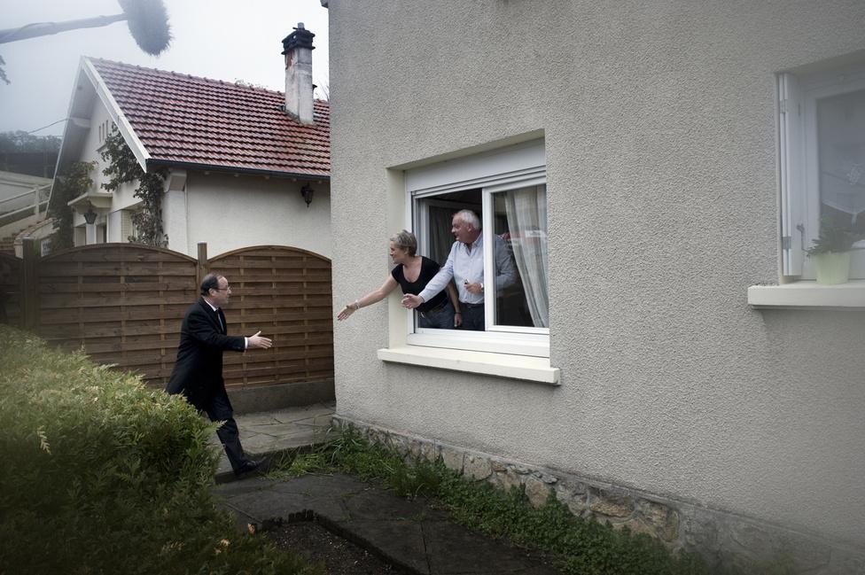 Egy séta alatt Bourges-ban Francois Hollande köszön a lakóknak az ablakon át. 2012. április 27.