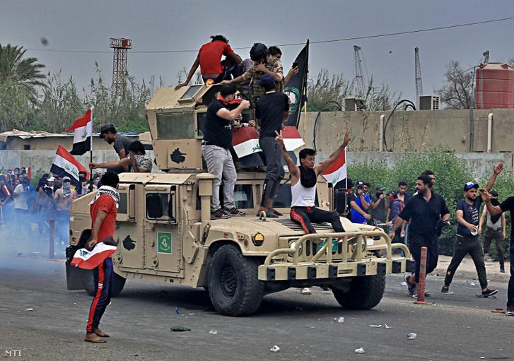 Kormányellenes tüntetők egy páncélozott katonai járművön Bászrában 2019. október 25-én.