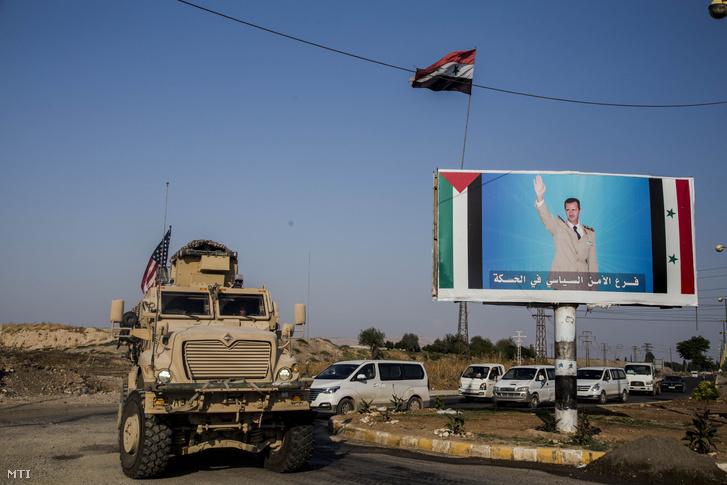 Bassár el-Aszad szíriai elnököt ábrázoló plakát mellett halad el egy amerikai katonai járműoszlop az észak-szíriai Kamisli térségében 2019. október 26-án.