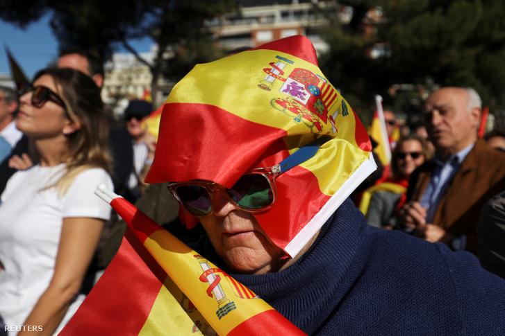 Egy spanyol zászlóba burkolózott nő a jobboldali Vox rendezvényén