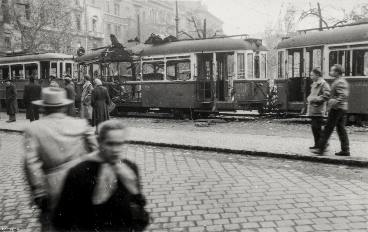 Kiégett villamoskocsik a József körúton, háttérben a Rákóczi tér házai. A forradalmárok sokszor barikádként használták a roncsokat.