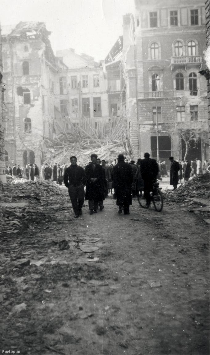 Sétálók az épülettörmelék között a Práter utca sarkából fotózva, szemben a József körút 81. romjai. Az egykori, környezetébe illeszkedő klasszikus bérház helyén ma egy hatvanas évekbeli épület áll.