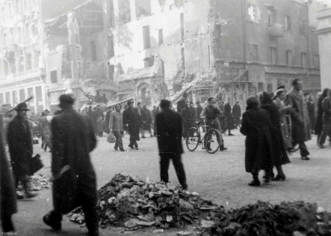 Tankok között hömpölygő tömeg a Rákóczi út és az Osvát utca sarkán október utolsó vagy november első napjaiban. A képen balra az egykori Athenaeum nyomda ma is álló épülete, a romos bérház helyén ma modern szálloda.