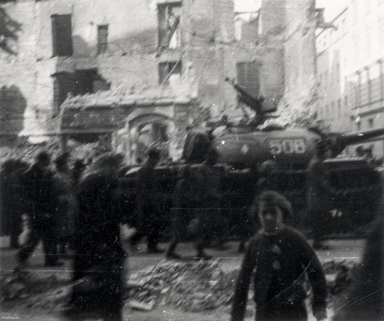Romok, sétálók és egy kilőtt szovjet tank a Rákóczi út és az Osvát utca sarkán, a Hauer cukrászda felől fotózva.A kilencéves kisfiúnak olyan volt ez a néhány nap, mint az addig csak családi elbeszélésekből ismert háború.
