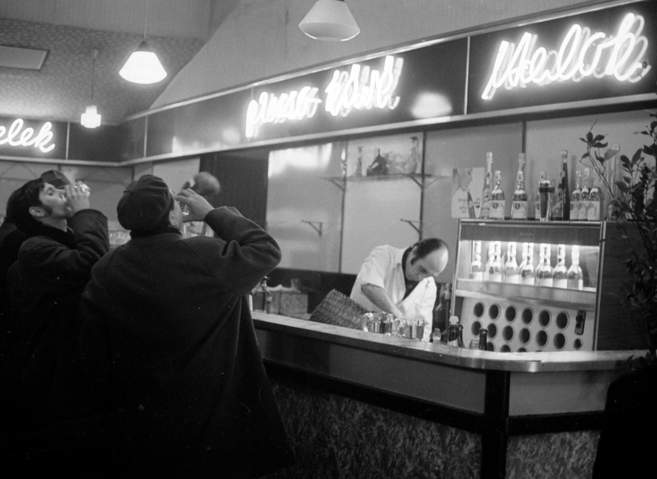"""Egy téli este Budapesten, 1974-ben. """"E pohár lesz a végső / ahogy aztán a pultra csapja / belerezeg a svájcisapka / kis antennája jelt ad és vesz / így járul hozzá az egészhez / részlegesen"""" (Parti Nagy Lajos képmelléírása)"""