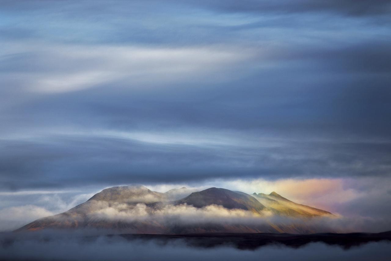 Tájak - 1. díj - Urbán Helga: Szivárvány-hegy - Öcsémmel éppen úton voltunk Izlandon a következő úti célunk felé, amikor megpillantottuk ezt a csodás jelenetet. Nem volt sok időm megörökíteni, hiszen mindössze néhány percig volt látható ez a különleges jelenség. És bár elsőre nem volt egyértelmű, hogy mi is okozza a színeket, végül kiderült, hogy egy szivárvány darabkáját láttuk a felhőrések között.