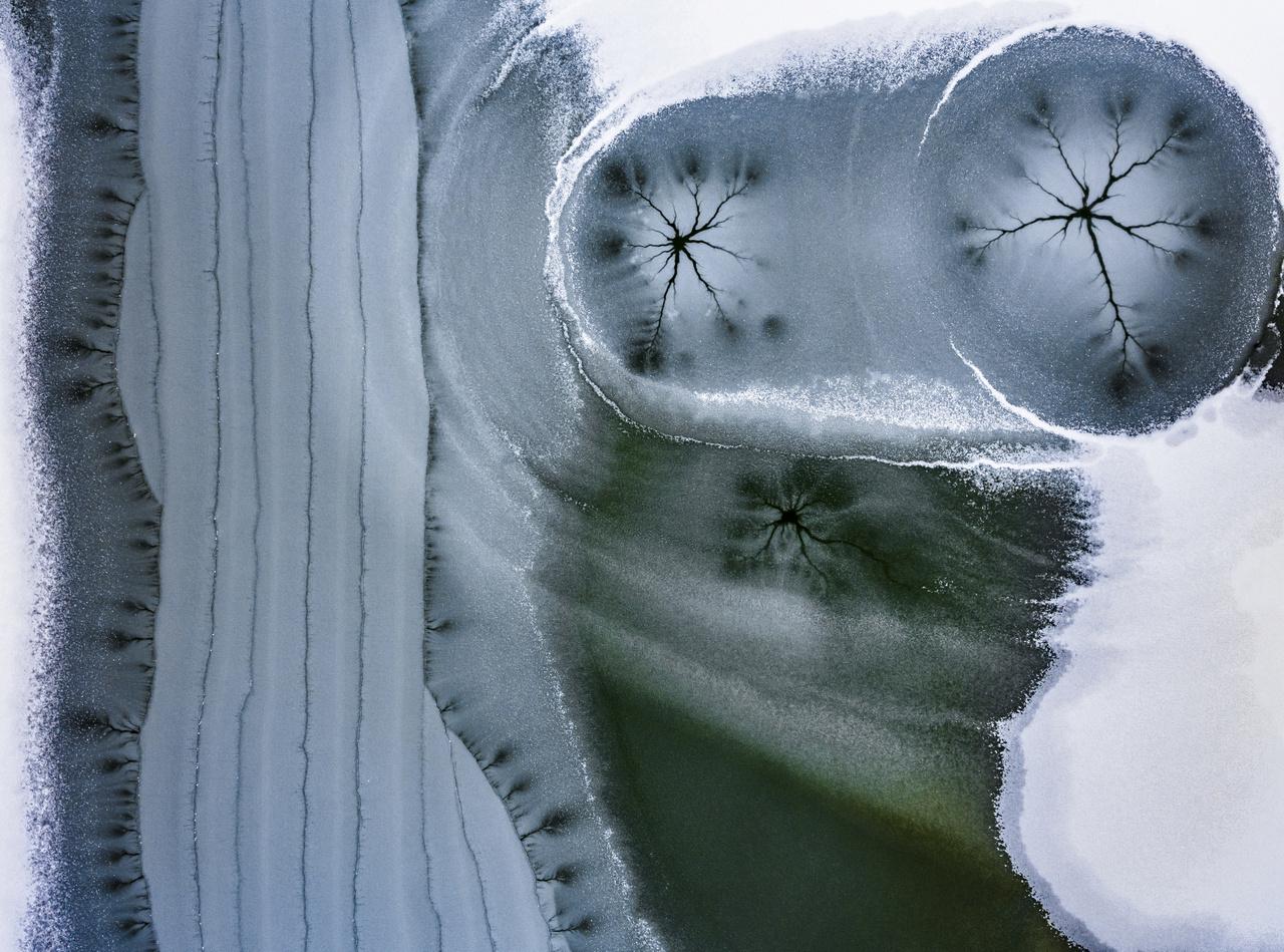 Kompozíció, forma és kísérletezés - Dícséretre méltó - Daróczi Csaba: Jégcsillagok - Ezeket a formákat már régóta figyelem, de sosem sikerült még jó képet készítenem róluk. A jégcsillagok akkor keletkeznek, amikor a jégre vékony hóréteg esik. 2018 utolsó napjaiban szerencsésen meg is történt ez, és gyönyörű formák keletkeztek. Így egyik nap munka után ki is mentem a városunk mellett fekvő tóhoz, és gyönyörű jégcsillagokat találtam rajta. Ezt a formát még sikerült lefotózni, de sajnos hamar besötétedett, így elhatároztam, hogy másnap reggel is itt kezdem a napot. Így is történt, de reggelre már teljesen máshogy festett a tó. A következő napokban a környék tavait jártam, és hihetetlenül érdekes formákat sikerült még fotózni ezekről a képzőményekről.