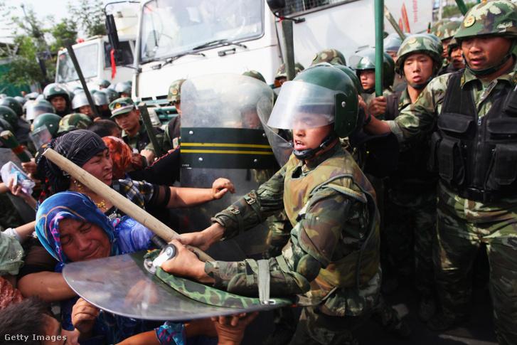 Rendőrök bántalmaznak ujgur nőket egy tüntetésen 2009-ben.