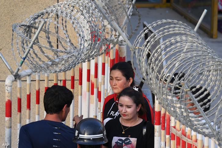 Egy ujgur nő lép be egy Kínai bazár bejáratán 2019. május 31-én Hotan városában.