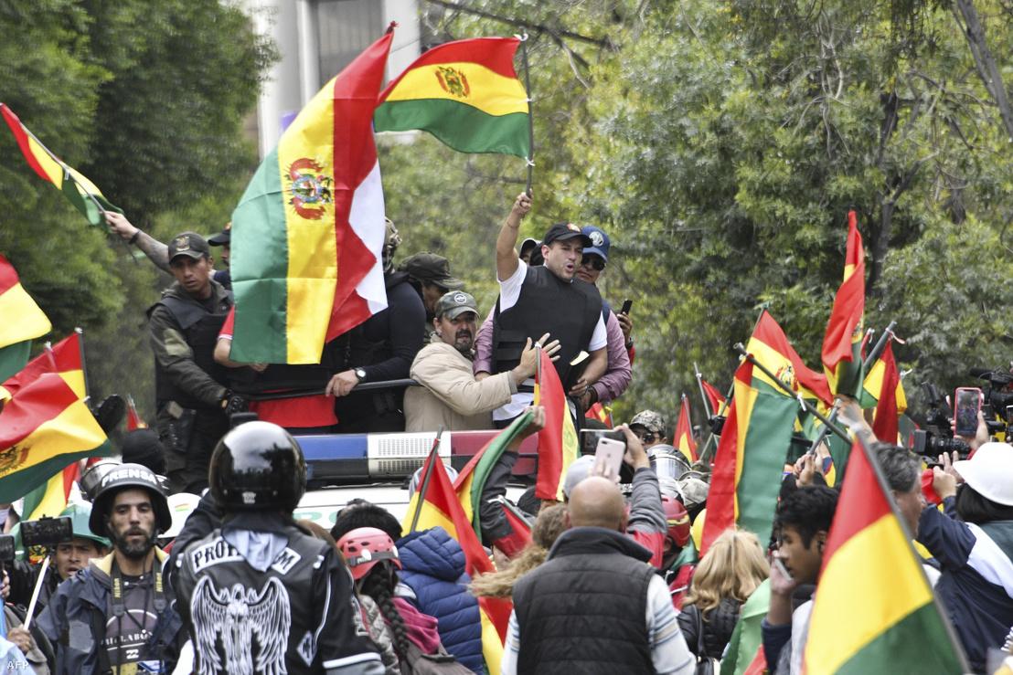 Luis Fernando Camacho az ellenzék vezetőja integet bolíviai zászlókkal körülvéve 2019. november 10-én