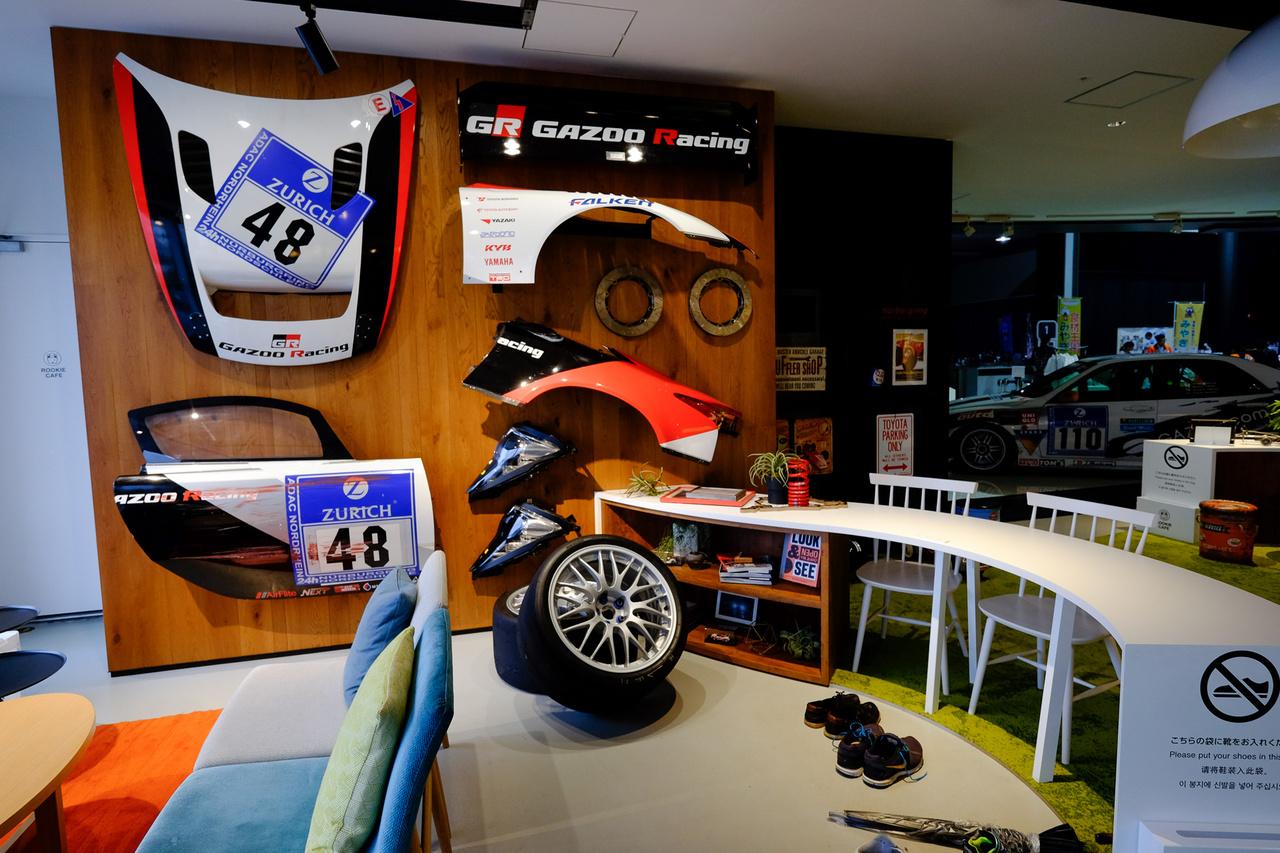 A kék szőnyeges, foteles pihenőrész egyik falának dekorációja mind versenyautó-karosszériaelem