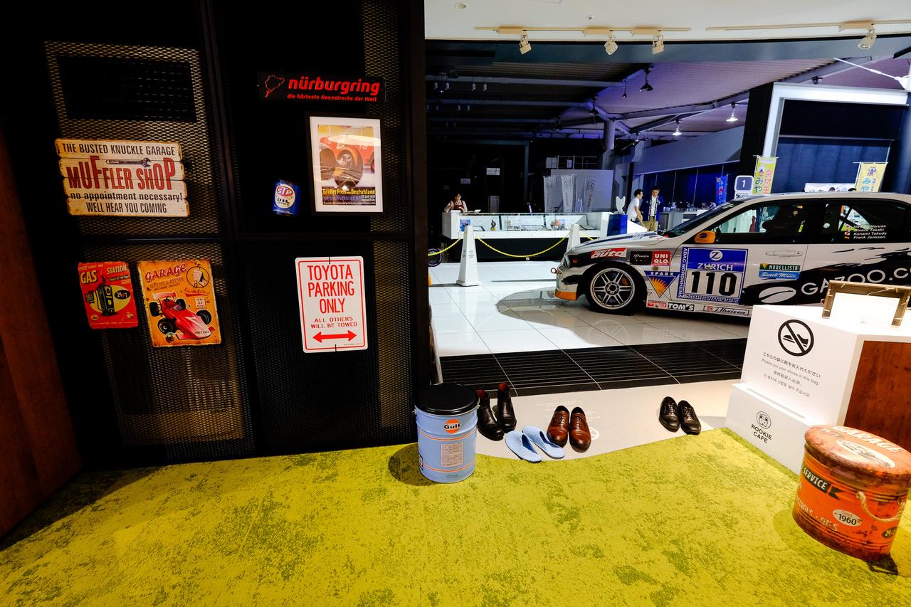 Cipőelhagyó hely pléhtáblákkal és egy Gazoo Racing-féle IS200-assal a háttérben