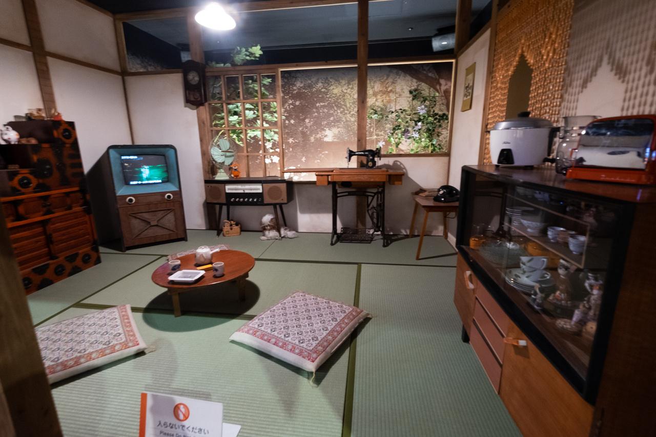 Japán lakásbelső a hatvanas évek elejéről. Tatami a padló, épp csak pár bútor, térdelőpárna, rövid lábú asztal, rizspapír falak - oké, ez többnyire ma is ilyen, pláne vidéken. De ott a színes, kis képcsöves tévé, a kenyérpirító, a mjúzik center, a rizsfőző... csupa-csupa modern vívmány
