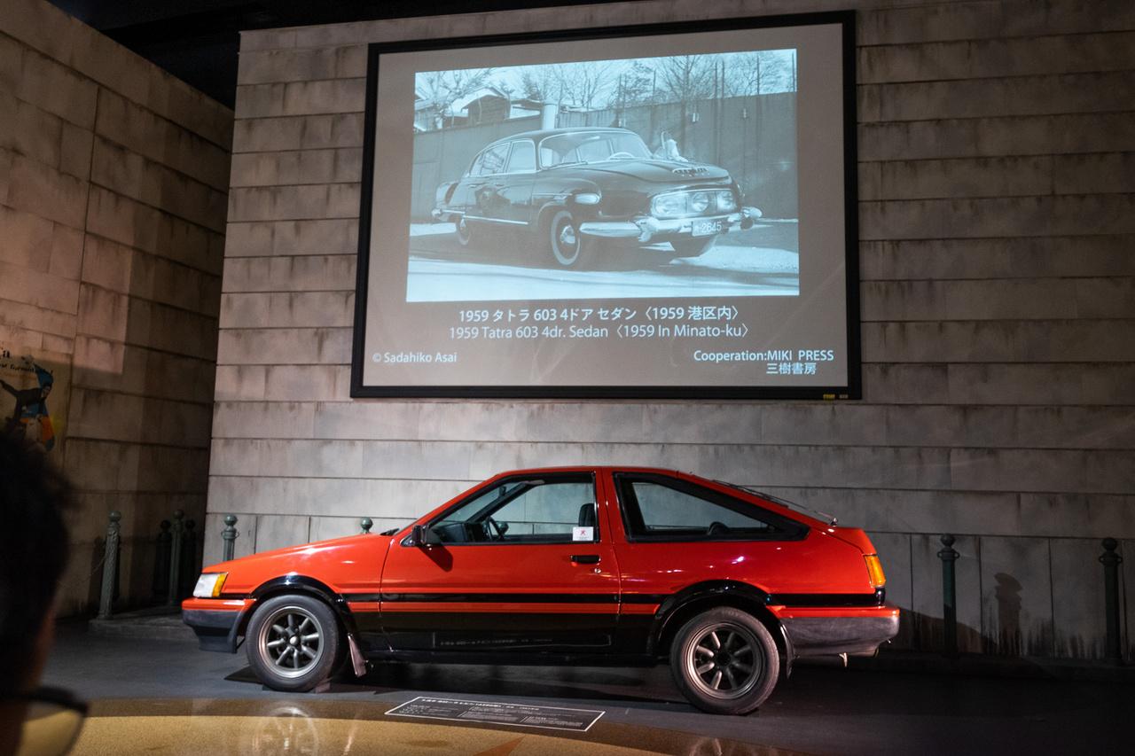 AE86 életnagyságban, méghozzá a Trueno-kivitel. Fölötte vetítés zajlik, japáni, érdekesautós utcaképekkel különféle szériákban - 50-es évek, 60-es évek, 70-es évek. Itt is el lehet ücsörögni egy órát. Az 1959-ben készült képen egy diplomata, háromszemű Tatra 603 a tokiói Minato-ku-ban, amely az egyik belső kerület