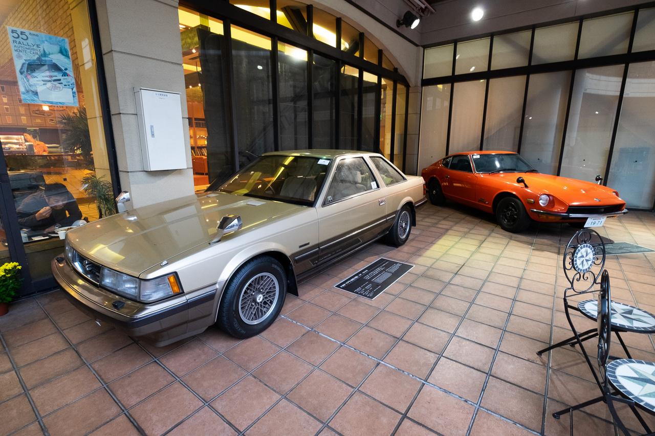 Kint, az udvarban, féltető alatt a Toyota Soarer és a Nissan 240Z. Utóbbi egy szentkehely-Z 432-es kivitel 1971-ből, amelynek az orrában 160 lóerős, kétliteres, sorhatos, 24-szelepes DOHC-motor van. A 432 jelentése: 4 szelep, 3 karburátor, 2 vezérműtengely