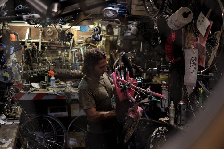 Egy kisgyerek új biciklijét szereli Rácz Kálmán, az adományok 90 százaléka szervezetekhez, például gyermekotthonokba kerül