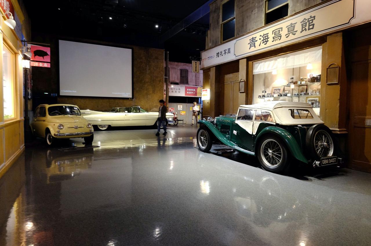 Csak a tükörsima padló miatt sejthető, hogy valami szupermodern pláza belsejében vagyunk, mert a körítés hitelesen lepukkant. 1945-ös MG TC parkol a régi japán fényképezőgépekkel teli kamerashop előtt (amiről a japánok híresek lettek)