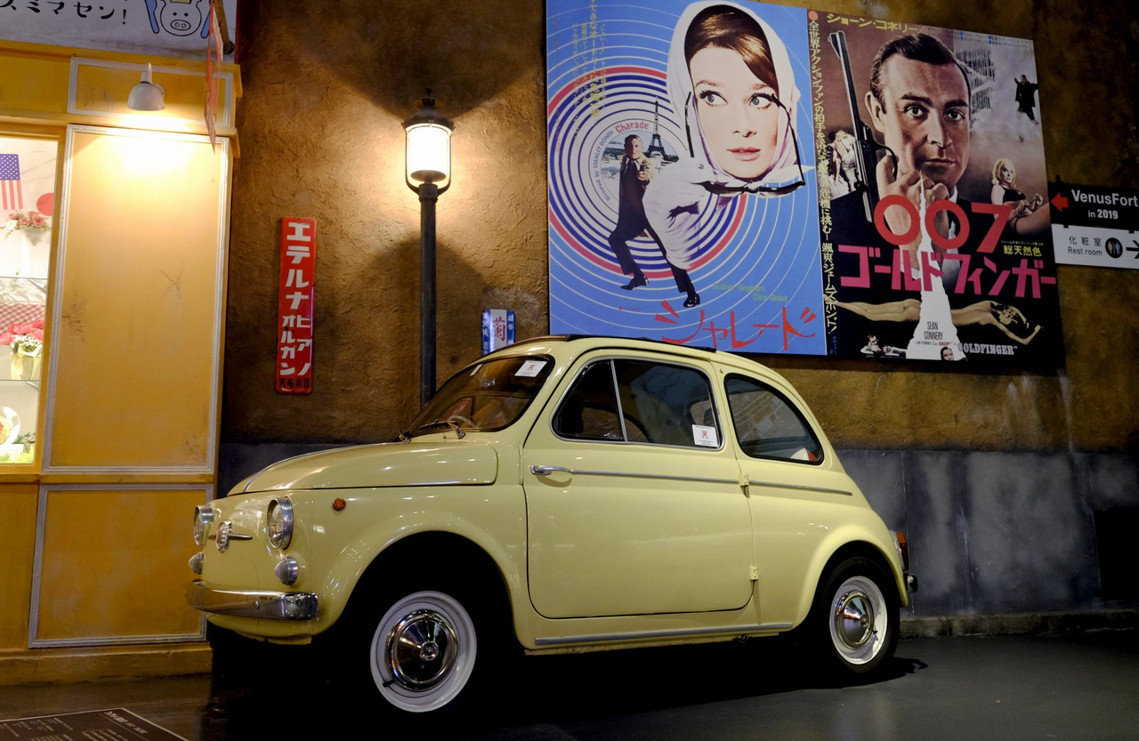 A Fiat 500 összes szériáját keverni szokták a kívülállók, de ezt itt nem szúrták el. 1960-65 között gyártott 500D (ez konkrétan 1962-es), még a libakergetős változat, fölötte stimmelő filmplakátok. Audrey Hepburn (A lány, aki ellopta az Eiffel-tornyot), Sean Connery (James Bond: Goldfinger), mindkettő 1964-ből