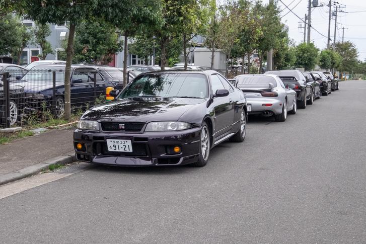 Az első sokk: az STF-műhely előtt kuncsaftok JDM-autói várnak tömött sorokban, legelöl egy R33-as Nissan Skyline GT-R, utána egy utolsó szériás Mazda RX-7. Mifelénk egyetlen hasonlóra is kialakul a csődület