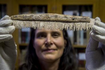 Hajdrik Gabriella régész technikus Tiszaug közelében talált egysoros csontfésűt mutat a Kecskeméti Katona József Múzeumban 2019. november 13-án