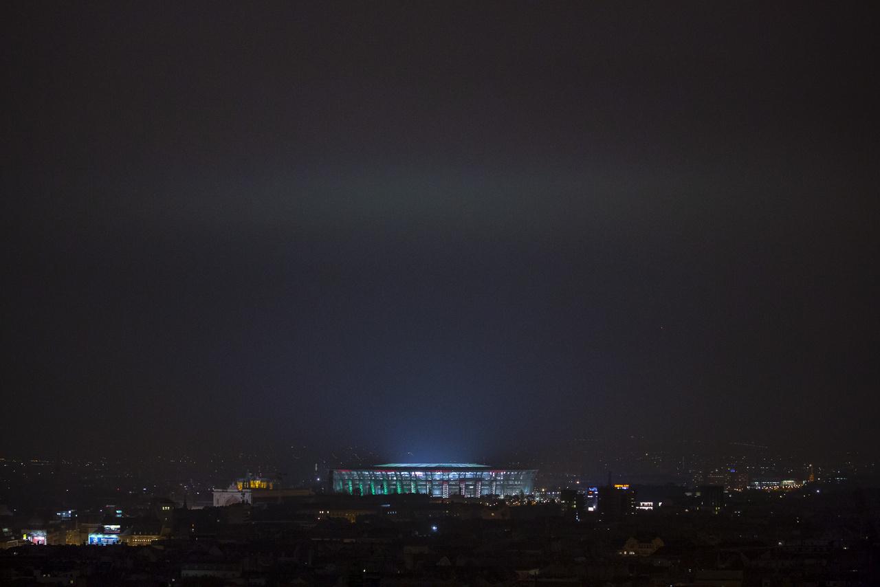 A díszkivilágítás színeit az alacsony felhőkre vetíti, így jelenhetnek meg a magyar zászló színei a stadion fölött az égen.